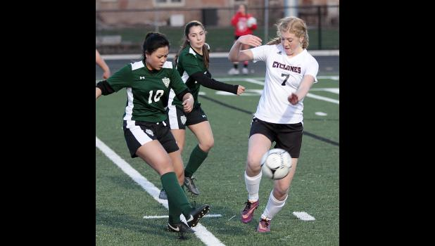 HCHS senior Jenna Brelje (7) attempts to block a kick by Sioux City West's Kim Ly during Friday night's match at Merrill Field. (Photos by Mike Oeffner)
