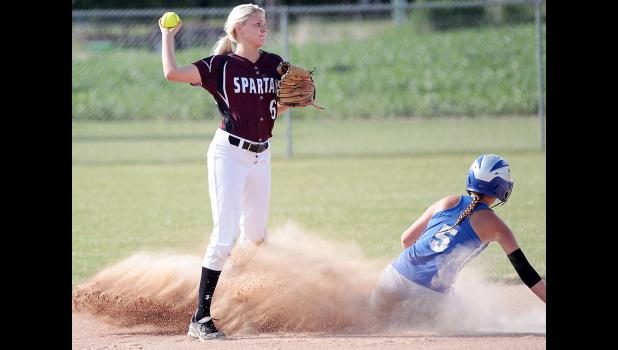 Exira-EHK second baseman Mara Burmeister (left) makes a relay throw to first after forcing out a sliding Emma Dorsey of CAM during Monday's regional softball game. The Spartans won 8-3. (Photos by Mike Oeffner)