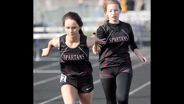 Exira-EHK's Camryn Paulsen hands the baton to Shelbi Wilson during the 4x800 relay. The Spartans placed second in the event during Monday's RVC Championships.