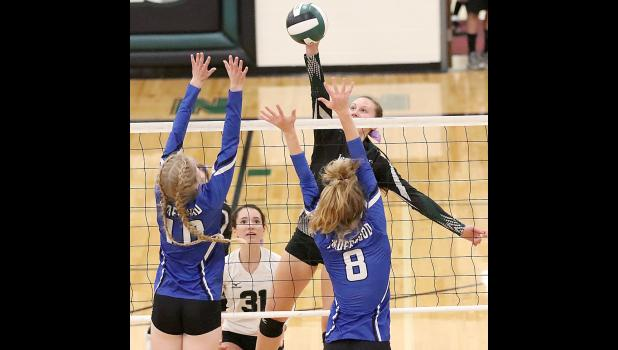 Gabby Cadwell hits over the Underwood tandem of Lauren Brown (10) and Peyton Cook (8) for one of her 17 kills on the night. (Photos by Mike Oeffner)