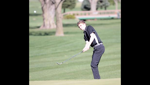 HCHS junior Kevin Campbell chips on to the green on the first hole.