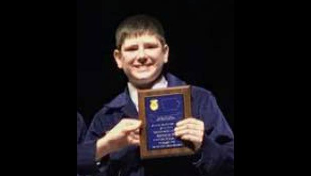 Carter Wagner receiving his plaque on stage in Hilton Coliseum for State Runner-up honors in the FFA Creed Speaking Contest.