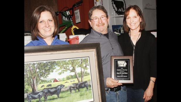 Cattleman of the Year, Gary and Ann Blum, Earling, along with the Cattlemen's Brandi Gubbels holding their scenic cattle photo.