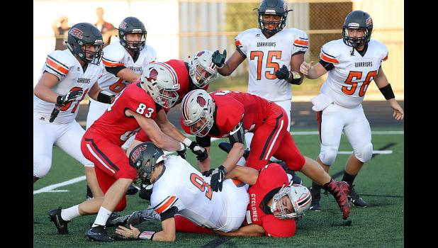 Sergeant Bluff-Luton quarterback Daniel Wright (9) is sacked by Harlan Community senior Brady Wagner (on turf) as Cyclones Jake McLaughlin (83) and Caleb Bieker also converge.