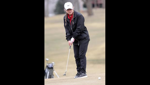 HCHS senior Delaney Kelly watches an uphill putt on the first green during Thursday's home meet.