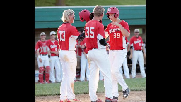 HCHS junior Ryan Doran (89) is greeted at home plate by Nick Foss (33) and Joshua Cheek (35) after clubbing a three-run homer in the second inning against Lewis Central.