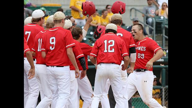 Harlan Community senior Ryan Doran (89) celebrates with his teammates at home plate after blasting a game-tying three-run homer in Friday's third inning.