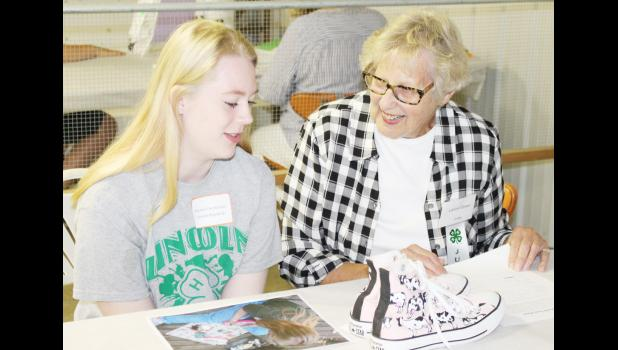 HARLAN -- Ainsley Christensen shows the changes she made to her Converse shoes to Judge Lavon Eblen. The shoes now have cows on them, and the project was categorized under the Family Consumer Science section of the fair. (Photo by Ryan Pattee)