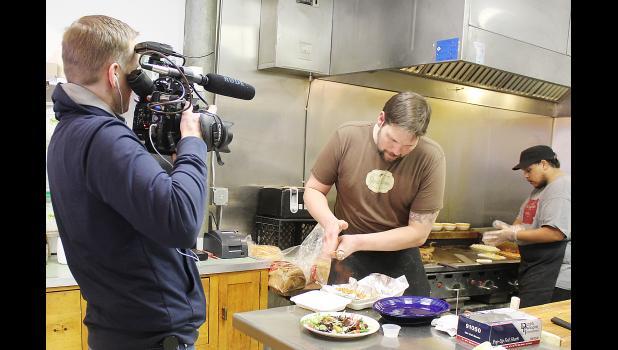 Chefs James Calkins and Caleb Darrington prepare a dish while cameraman Cameron McCoy films.