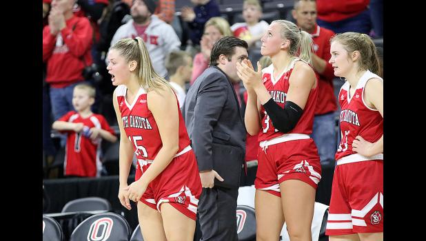 Taylor Frederick (left), a 2016 Harlan Community graduate, encourages her Coyote teammates from the bench against Omaha. (Photos by Mike Oeffner)