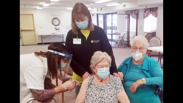 Geraldine Swisher gets her first dose, while assisted living manager Kathy Goede (standing) helps and Loretta Baughman awaits her turn.