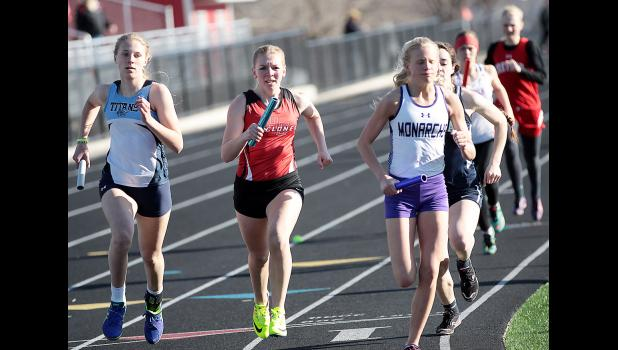 Cyclone junior Molly Gubbels (center) runs the 400-meter leg of the team's distance medley relay, which placed second. (Photos by Mike Oeffner)