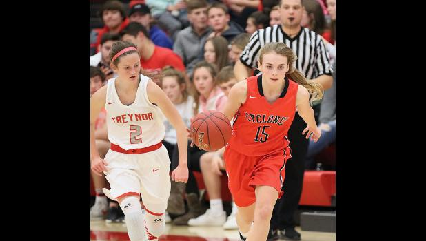 HCHS sophomore Ashley Hall (right) advances the ball past halfcourt as Tori Castle defends for Treynor.
