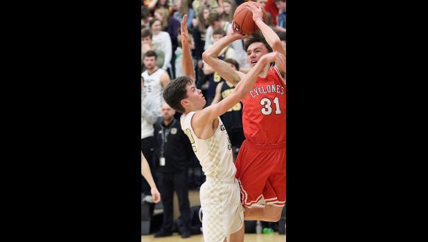 HCHS junior Michael Heithoff attempts an off-balanced shot over Glenwood's Dax Lappala. Heithoff scored nine points.