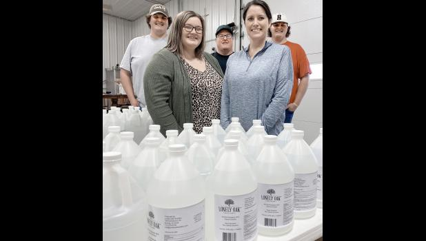 The Hoffmann family stands in front of one of their most recent batches of hand and surface sanitizer. The 160 proof product is a FDA approved recipe of denatured alcohol, glycerin, hydrogen peroxide and purified water.  Front, l-r, Lexi and Amy Hoffmann. Back, l-r, are Dave, Pat and Will.