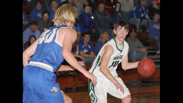 IKM-Manning senior Jared Johnson (14) looks to drive as Derrick Schorg (40) defends the lane for Remsen St. Mary's.