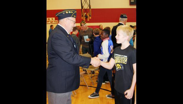 Sam Bladt thanks veteran Ken Olson of Harlan for his service.