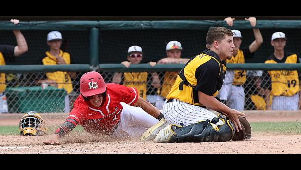 HCHS senior Logan Klaassen slides home safely with a sixth-inning insurance run as Waverly-Shell Rock catcher Carter Langreck waits for the relay throw.