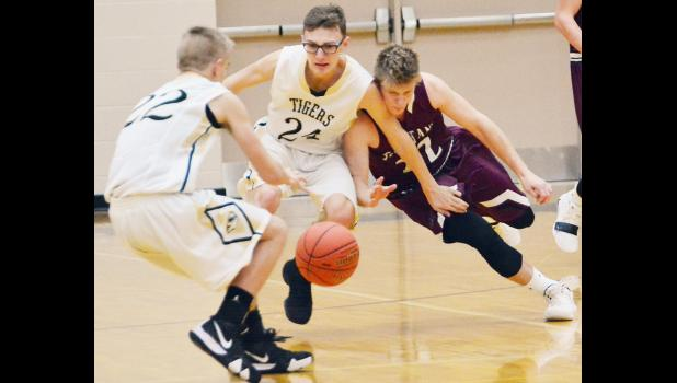Exira-EHK senior Ian Leader (right) battles for a loose ball with Woodbine's Seth Gruver (24) and Adam Sherer (22).
