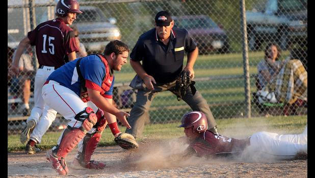 Exira-EHK's Cole Madsen slides home safely on Cole Burmeister's two-run single as Earlham catcher Gavin Boyle attempts to handle the relay throw. Spartan senior Cole Bruns (15) also scored on the play during Friday night's 11-1 victory.