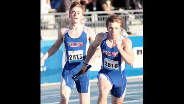 AHSTW senior Jake Martin (left) and junior Korbin Martin complete the second exchange of the 4x100 relay, which placed 11th at the Drake Relays Friday.