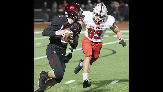 HCHS defensive end Jake McLaughlin (83), who finished the game with seven tackles for loss, chases after ADM quarterback Tate Stine-Smith during Friday's second half.