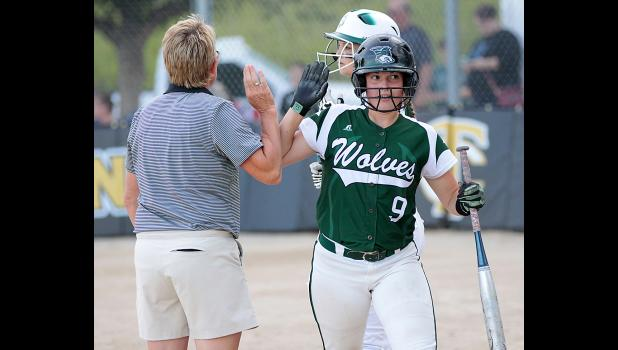 IKM-M eighth grader Zoey Melton (9) is greeted by Coach Joy Gross after scoring a run. (Photos by Mike Oeffner)