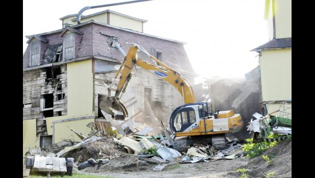 Bobby Fox from Fox Construction tears down a portion of the old mill in east Harlan last week.