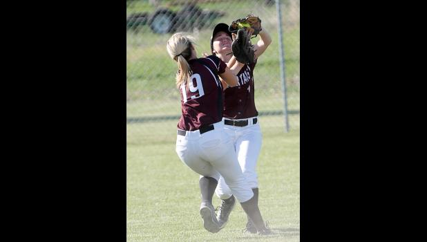 Spartan center fielder Kealey Nelson catches a fly ball as she nearly collides with Sophia Peppers (19).