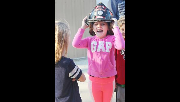 Lily Muenchrath tries on a fire helmet as classmate Henry Schaben (far right) waits his turn in background.  The two are students at the Shelby County Catholic School.
