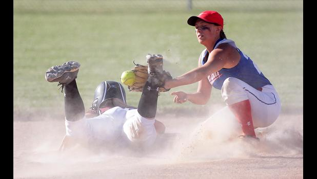 Spartan junior Sophia Peppers dives back safely into second base ahead of the throw to a Bobcat infielder.