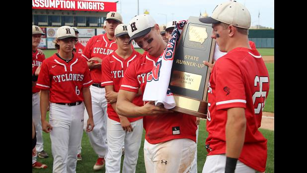 Harlan Community seniors Logan Klaassen (right) and Ryan Doran hold up the Cyclones' Class 3A state runner-up trophy and banner following Saturday's 11-1 loss to Davenport Assumption at Principal Park. Among those looking on are Nick Foss (left), Kelby Lasher (6), Derec Weyer and Jacob Bartley.