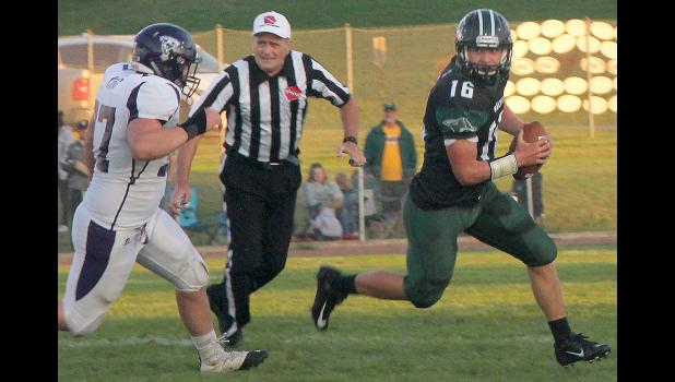 IKM-M quarterback Kyler Rasmussen eludes the pass rush of a Titan lineman. (Photos by Kim Wegener)