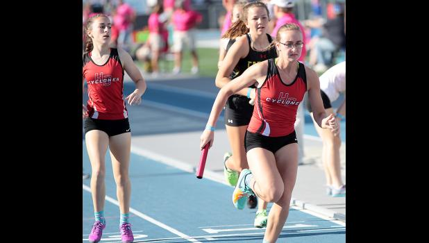Senior Kara Rueschenberg (right) runs a leg of the HCHS girls' 4x800 relay, which placed 22nd. At left is sophomore Abby Alberti.