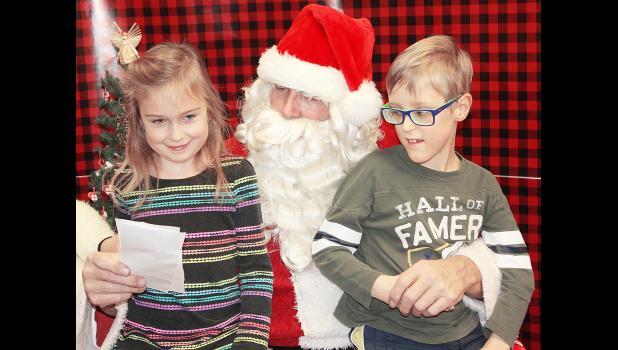 ELK HORN -- Mary Eldal and her brother, Alex Eldal, listen as Santa Claus reads through their Christmas wish list.  (Photo by Kim Wegener)