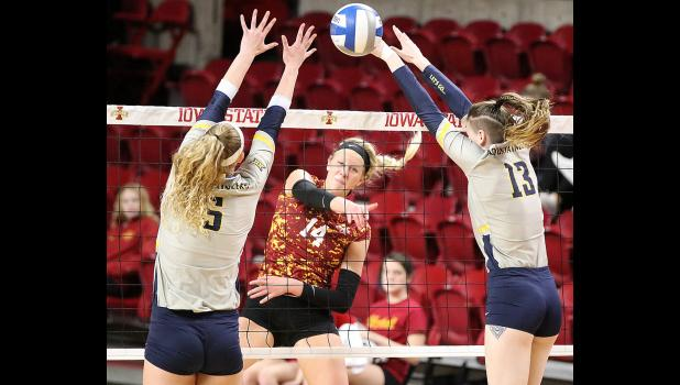 KILLER IN CAMO -- Iowa State senior Jess Schaben (center) delivers a spike between two West Virginia blockers during a November 10 home match. Schaben led the Cyclones in kills all four seasons at ISU and finished fourth in program history with 1,548 career kills. She was just the third Iowa State player to surpass 1,500 kills and 1,000 digs. (Photos by Mike Oeffner)