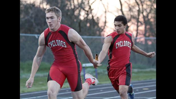 Harlan Community's Austin Smith (right) and Jake McLaughlin execute the first exchange of the Cyclones' 4x100 relay, which placed third.