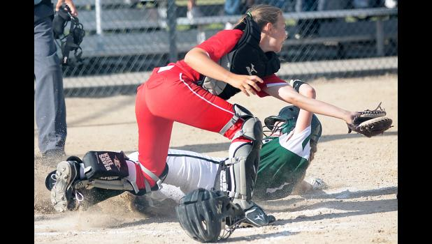 IKM-M junior Payton Sporrer slides home safely with the first run of the game as Lady Red catcher Kylie Wilson takes the throw.