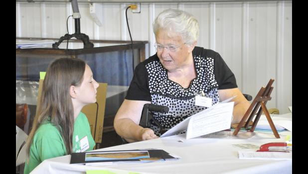 HARLAN -- At the 4-H Static Exhibit judging, Caitlyn Dills showed her photography entries to Rita Faust, one of the photography judges. Tuesday was the first day of judging at the fair.