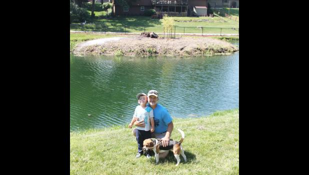 Emmett and Steven Olson stand with their dog Otis in front of the Pioneer Park island that they helped clean up. (Photo by Sarah Muller)