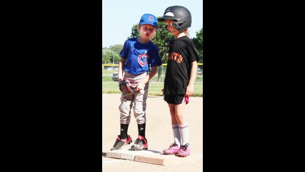 Audrey Scheuring (left) stands on first base talking to Hadley Gross.