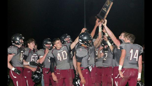 Spartan players hoist their playoff trophy following Friday's game.