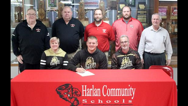 Derec Weyer (front row, center) is seated next to his parents, Tim and Kelli Miller. Back row, left-right: HCHS head football coach Curt Bladt and assistant coaches Mark Kohorst, Sam Brummer, Todd Bladt and John Murtaugh. Not pictured: Derec's parents Shane and Missy Weyer. (Photo by Mike Oeffner)
