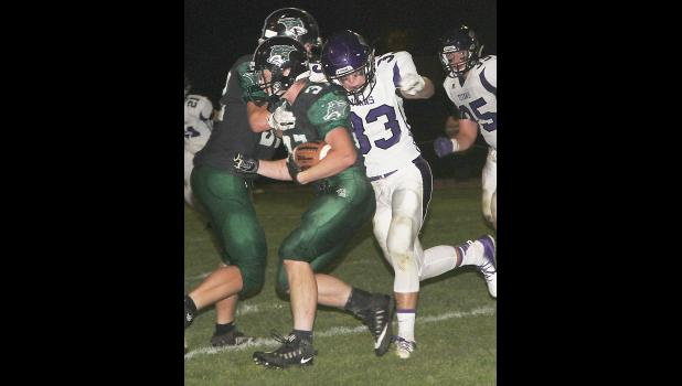 Keaton Allmon runs the football for IKM-M as Brennan Holder looks to make the tackle for South Central Calhoun.