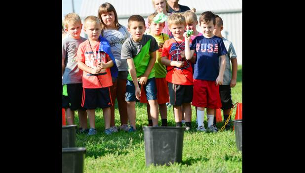 """One of the fun things for kids was learning how to pick up manure!  They got a prize if they could successfully toss the """"end result"""" in a bucket."""