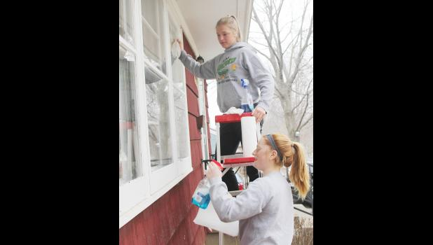 Makenzie Jones (top) and Rachel Blum wash some windows for a homeowner.