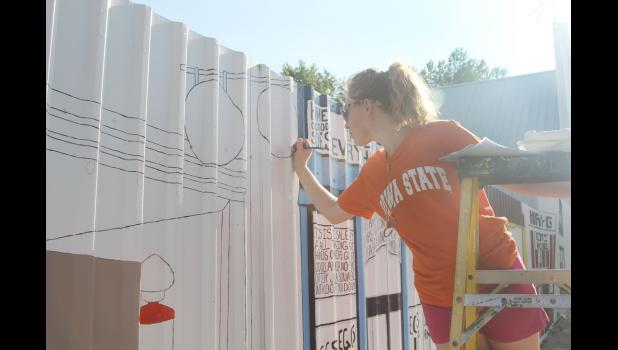 Becca Stein has been working on painting the mural on the large fence along Main Street in Portsmouth.  The mural is a welcome addition to the community.  (Photo by Sarah Muller)