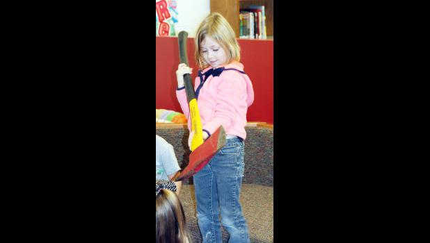 Kindergarten student Edyn Stinn takes a look at a fireman's ax during a fire prevention program at the Harlan Community Primary Building on Tuesday.