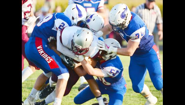 A Mustang ball carrier is tackled by several Viking players.