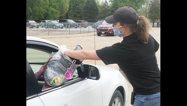 Families picked up their belongings last week at the Harlan Community Elementary Schools.  Teachers/associates gathered up the belongings from desks and lockers for distribution after the school buildings were closed. Lori Tarney hands back items.